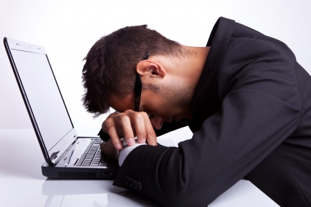 sleeping at desk: Tired business man with head and hands down on laptop