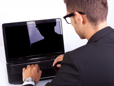 back view of a business man working at his laptop computer photo