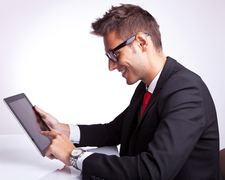 web side: side view of a young business man browsing on his tablet pad  Stock Photo