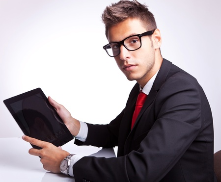 side view of a young business man holding his tablet pad and looking to the camera photo