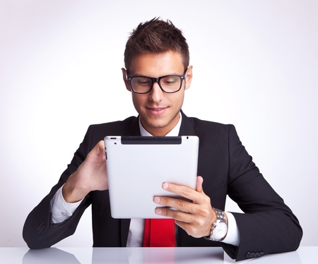 business man choosing something on his pad by tapping it's touchscreen Stock Photo - 15500403