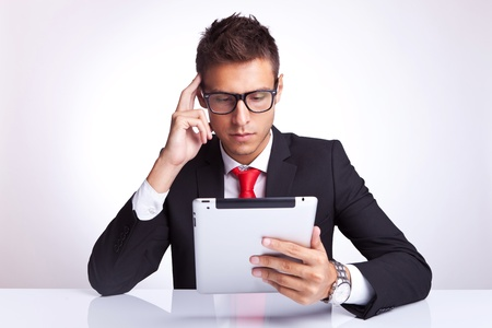 well read: business man contemplating at what he is reading on his new tablet pad Stock Photo
