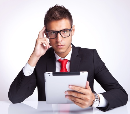 portable information device: serious and thoughtful business man holding an electronic tablet pad and looking to the camera