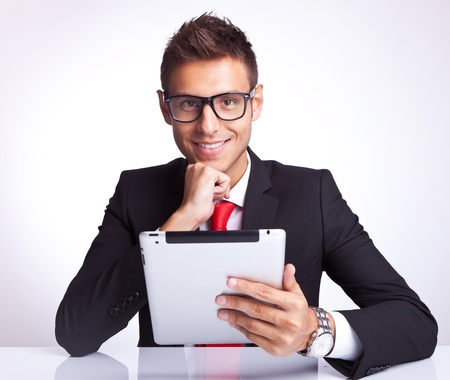pensive business man smiling to the camera while holding an electronic tablet pad  photo