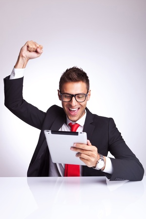 joy pad: young business man wearing glasses screaming of joy while reading the good news on the tablet pad Stock Photo