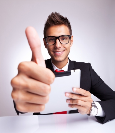 young business man making the ok thumbs up gesture while readin on his tablet pad photo