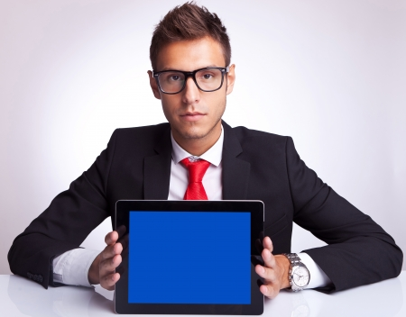 business man showing an electronic pad while sitting at his desk photo
