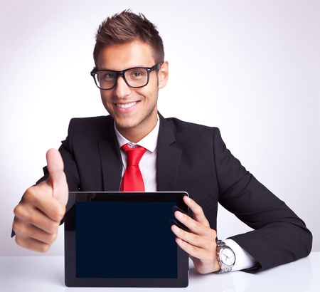 Office worker holding blank digital tablet pad and making ok hand gesture photo