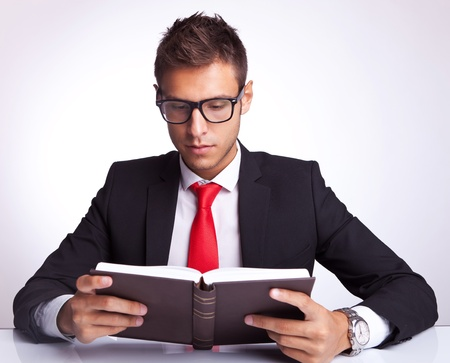 adults learning: young business man wearing glasses reading a book at his office desk Stock Photo