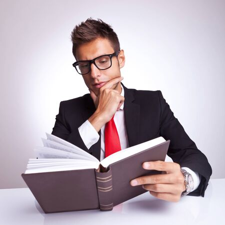 intrigued: intrigued business man reading a book and wondering what will happen next