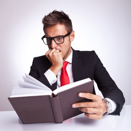 affraid: young business man being affraid by the action or subject of the book he is reading