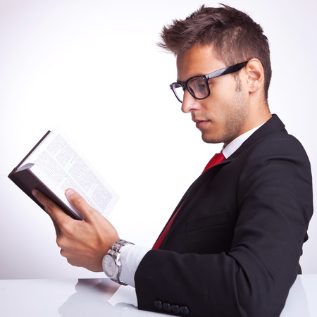 side view of a business man reading an interesting book at his desk