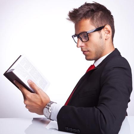 gafas de lectura: Vista lateral de un hombre de negocios la lectura de un buen libro en su escritorio Foto de archivo