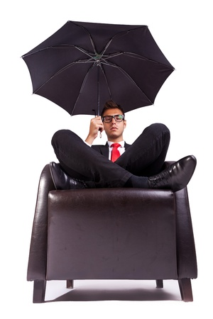 black business men: Image of a business man sitting in comfortable armchair with an umbrella in his hand Stock Photo