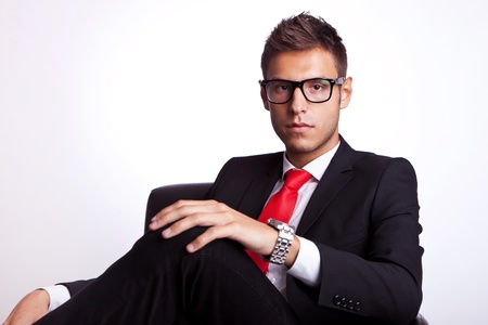 serious young business man wearing glasses and sitting in an armchair photo
