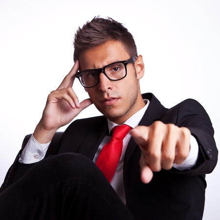 accusing: angry  business man sitting in a chair pointing his finger accusing you