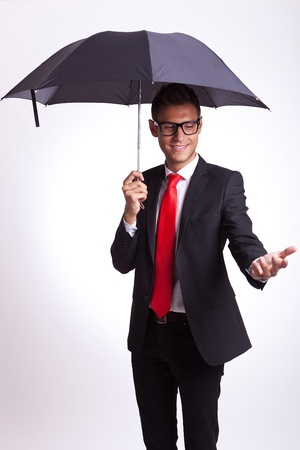 handle: young business man reaching and checking with his hand if it rains Stock Photo