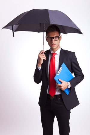 young business man holding an umbrella and ra blue notepad photo