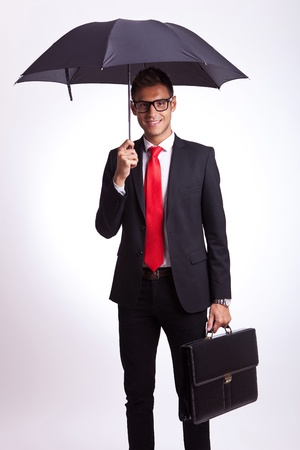 cautious: young business man holding an umbrella and a suitcase, smiling to the camera