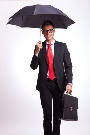 suit case: smiling business man under an umbrella walking towards the camera on gray background Stock Photo