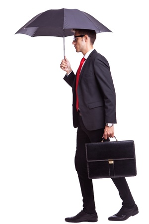 cautious: side view of a young business man holding an umbrella and a briefcase Stock Photo