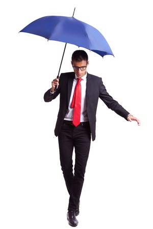 young business man in an equilibrium act, helped by an umbrella, walikng forward photo