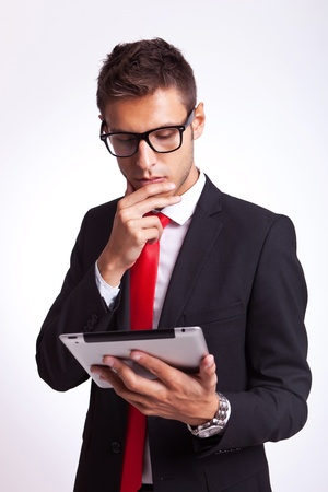 he: young business man is intrigued by the news he is reading onhis new tablet pad