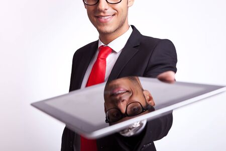 closeup of a young business man offering to you a brand new touch screen pad photo