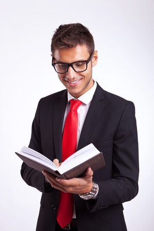 holding bible: Handsome young man in a suit reading an interesting book and smiling