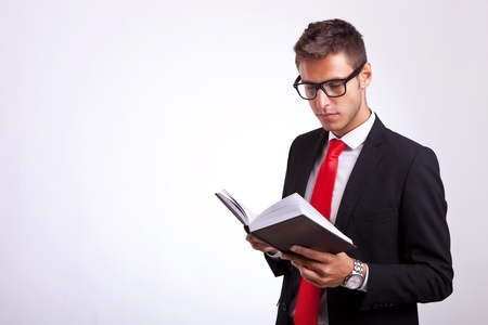 young student wearing glasses and reading a law book on grey background photo