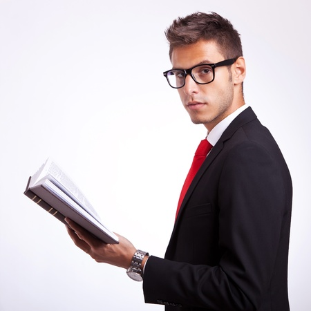 side view of a young student holding a book and looking at the camera Stock Photo - 15500477