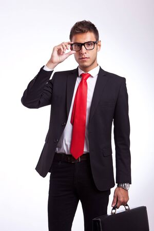 young business man or student holding his glasses and looking at the camera photo