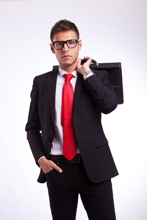 serious business man with his briefcase on his back looking at the camera Stock Photo - 15500285
