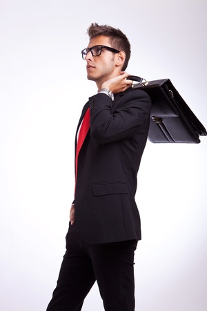 business briefcase:  profile of a young business man or student looking to his side with suitcase on his shoulder