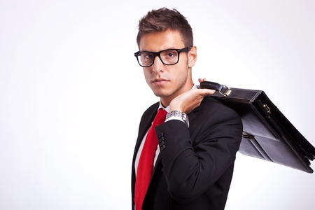 young student wearing glasses and looking at the camera, holding his briefcase on his back photo