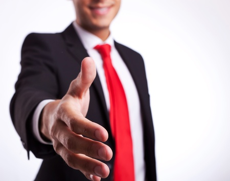 business partner: young business man or student ready to handshake, welcoming you Stock Photo