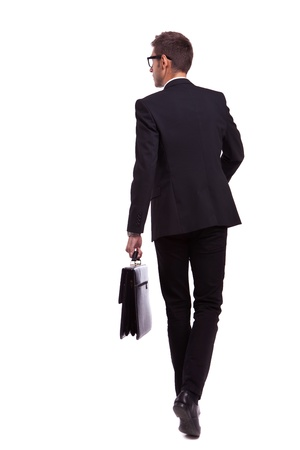 suit case: back view of a walking business man holding a briefcase and looking to his side on white background  Stock Photo