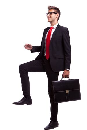 business man  holding a suitcase stepping up and forward photo