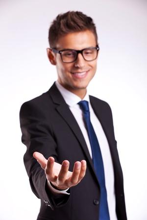 manos abiertas: joven hombre de negocios con gafas y sosteniendo algo en su mano