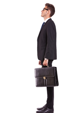 business men: side view of a young business man or student looking up - full body picture