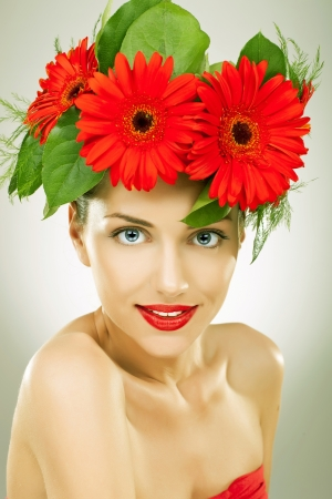 gracefully: gracefull young woman with red gerbera flowers in her hair looking and smiling to the camera Stock Photo