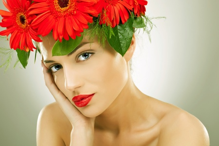 gorgeous seductive woman wearing flowers in her hair holding her head in her palm photo