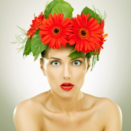 amazed young woman with red gerbera flowers on her head looking at the camera photo