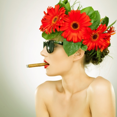 side view of a relaxed sexy woman with cigar in her mouth and wearing red gerbera flowers on her head