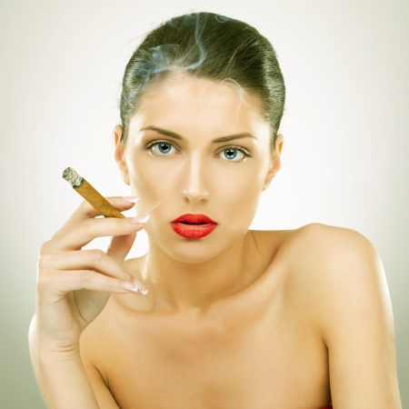 portrait of attractive young woman smoking cigar, studio background photo