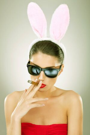 sexy bunny woman wearing sunglasses smoking on a big cigar photo