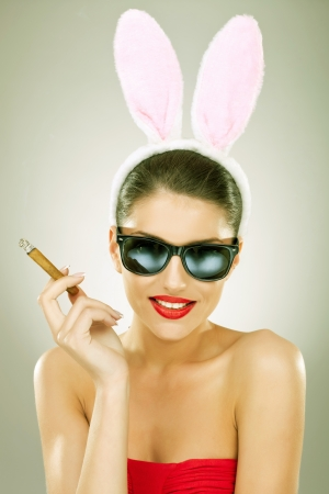 smilling beautiful bunny woman wearing sunglasses and smoking cigar - vintage style picture photo