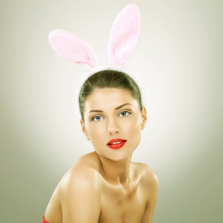 vintage look picture of a beautiful young woman wearing bunny ears and smiling to the camera photo