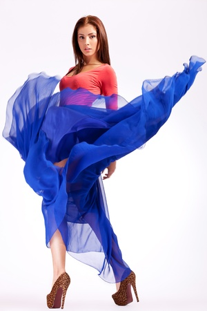 fluttering: sensual young woman in a blue fluttering dress looking at the camera