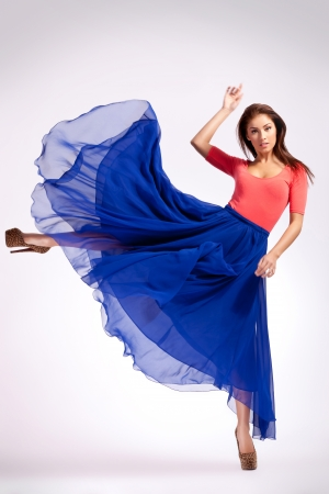 high fashion: young woman in blue dress kicking to her side and looking at the camera